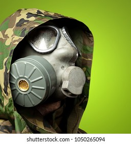 closeup of a soldier wearing a gas mask against a green background