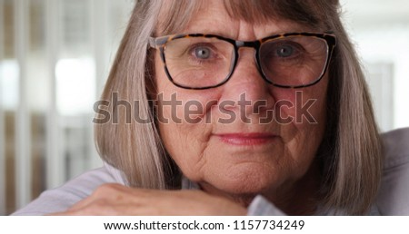 55626bd2f31 Close-up of somber elderly woman wearing eyeglasses in modern indoor setting