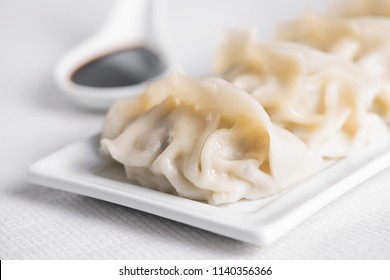 closeup of some asian jiaozis or gyozas on a white ceramic plate and a white ceramic spoon-shaped bowl with soy sauce, on a table set for lunch or dinner