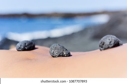 closeup of a some black stones on the back of a young man lying down on the beach in the summer