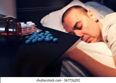 closeup of some different pills in the nightstand and a young man laying face down in bed with his eyes closed, at night