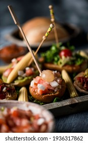 closeup of some different vegan spanish pinchos, made with bread with different toppings, and topped with skewers, served as snacks or appetizers on a wooden tray, on a gray rustic wooden table