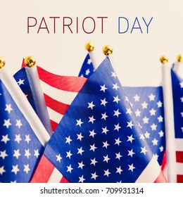 closeup of some flags of the United States and the text patriot day against an off-white background