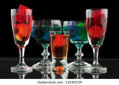 closeup of some glasses with cocktails of different colors in nightclub