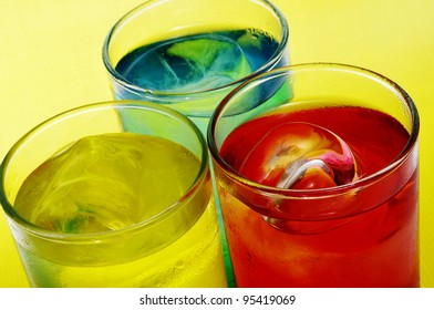 closeup of some glasses with mixed drinks on a yellow background