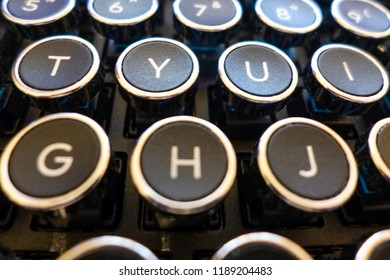 A close-up of some of the letter keys in an antique style QWERTY layout typewriter keyboard.