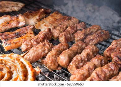 A closeup of some meat skewers and beef sausages being grilled on a barbecue with smoke