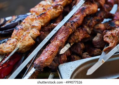 the closeup of some meat skewers being grilled in a barbecue. grilled meat skewers, barbecue