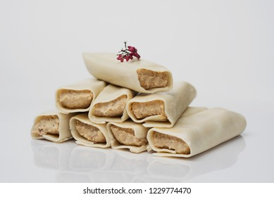 closeup of some meat stuffed cannelloni on a white background