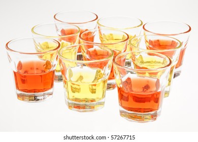 Closeup of some orange and yellow drinks served in mini glasses over a white background