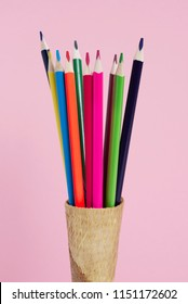 closeup of some pencil crayons of different colors in an ice cream cone on a pink background