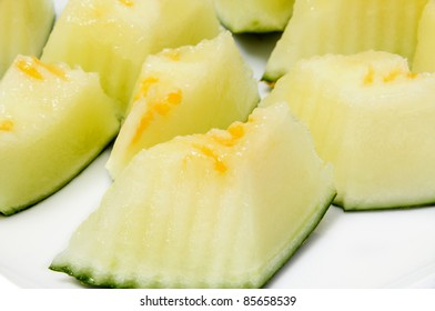 closeup of some pieces of melon on a white background