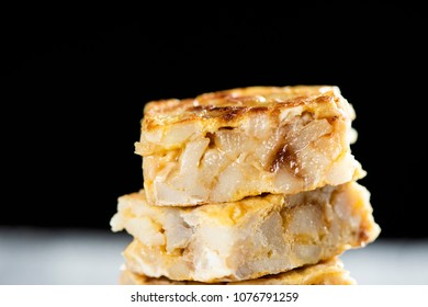 closeup of some pieces of typical tortilla de patatas, spanish omelet, on a rustic wooden table, against a black background