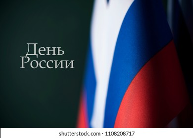 closeup of some russian flags and the text 'russia day' written in russian against a dark green background