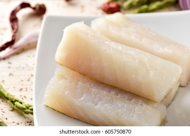 closeup of some slices of raw codfish in a white ceramic plate, on a rustic wooden table