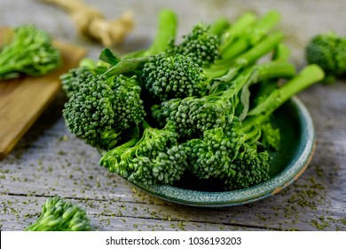 closeup of some stems of broccolini in a green ceramic plate placed on a gray rustic wooden table