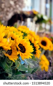closeup of some sunflower bouquets on sale on the street at the entrance of a florist shop