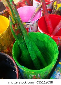 Closeup of some used Paint brush with different color pots