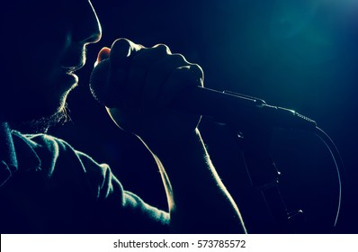 Closeup Songer hand holding the microphone and singing on black background with lens flare from spot light, musical concept