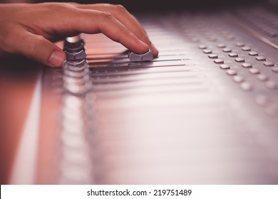 Close-up of sound engineer working on music mixer in the recording studio
