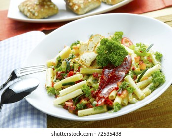 Close-up of an Spanish pasta meal with chorizo  penne tomatoes, meat sauce,rosemary, parsley and chili