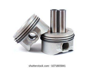 Close-up of spare parts two new pistons with connecting rods for a gasoline engine with installed sets of piston rings on an isolated white background