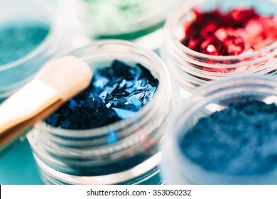 closeup of sparkling glitter eyeshadow set. Collection of  colorful shiny green, red and blue shadows. Makeup artist background.