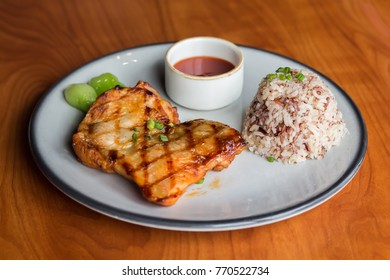 Close-up Spicy Chicken steak with rice in white plate on wooden table. with copy space.