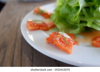 Closeup of spicy salmon salad on a white plate prepared for eat.