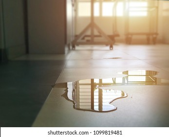 Close-up of spilled water in building with the ray of sun light. Wet floor from rainy splash or pipelines water leakage in house. Accident at home from slippery floor concept.