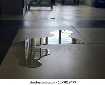 Close-up of spilled water leak on the floor of building. Wet floor from rainy splash or pipelines water leakage in office. Danger accident at home from liquid slippery floor hazard concept.