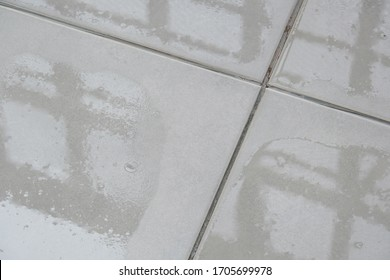 Close-up of spilled water leak on the floor of building.