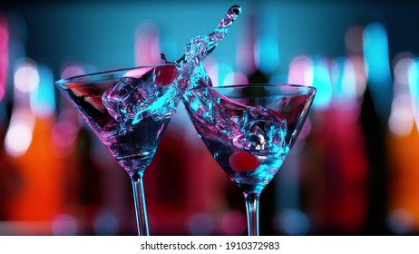 Closeup of splashing martini cocktails in cheers gesture. Bar on background, free space for text