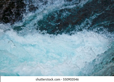 Closeup of splashing water below rapids on the cold, glacial fed McKenzie River in Oregon.