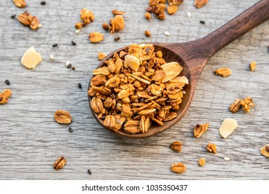 Closeup spoon with crunchy granola or muesli scattered healthy diet breakfast, top view background.