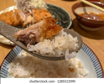 Closeup to a spoonful of rice and tonkatsu (pork cutlet) with dish of tonkatsu (pork cutlet) in background