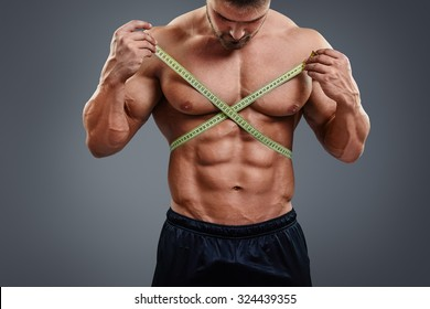 Closeup of sports man measuring his waist with a tape measure. Bodybuilder with sexy six packs abs measures gain in waist isolated over gray background.