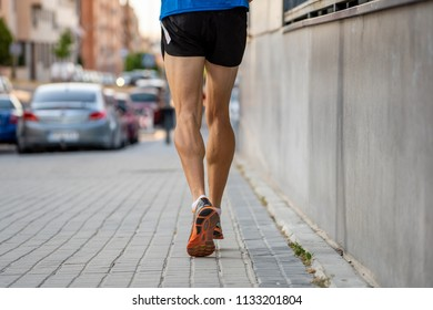 Closeup of sports mans legs running with sport background urban city backdrop in runner fitness concept with copy space