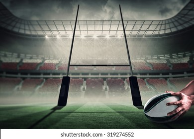 Close-up of of sports player holding ball against rugby pitch