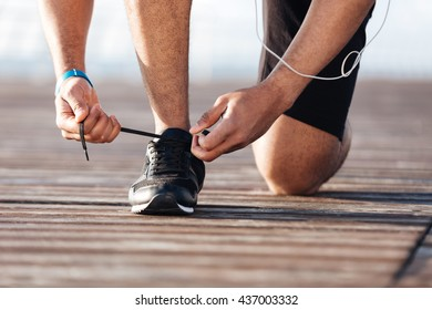 Closeup of sportsman laces his sneakers on pier