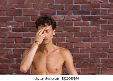 closeup of sporty man with naked torso making Alternate Nostril Breathing exercise, nadi shodhana pranayama pose working out, indoor close up image. brick wall background with copy space