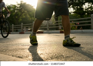 Close-up of sporty man running on the road in the City park against a beautiful orange sunrise in early morning