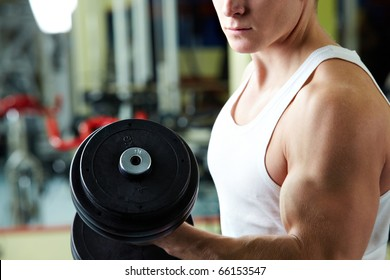 Close-up of sporty man training in gym with barbell