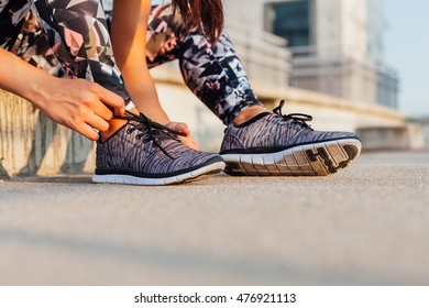Closeup of sporty woman binds the laces on shoes on the street before exercise