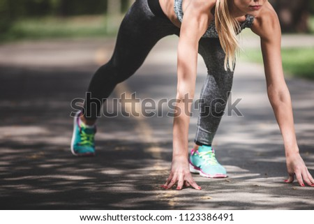 Close-up of sporty woman in crouch start on sunny road. Female is feeling very concentrated before fast running. Training endurance outside concept