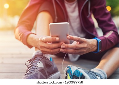 Closeup sporty woman hand using smartphone while sitting on floor. Woman wearing jacket and typing on mobile phone to check pulse rate. Runner hand using smart phone while sitting on ground after run.