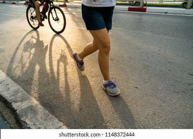 Close-up of sporty woman running on the road in the City park against a beautiful orange sunrise in early morning