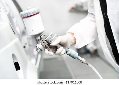 close-up of spray gun painting a car