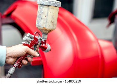 Close-up of spray gun with red paint painting a car in special booth