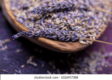 Closeup of sprigs of lavendar and scattered flowers in and around a wooden scoop.